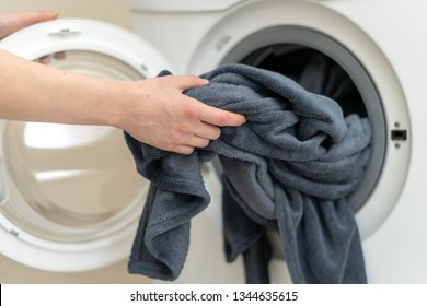 Cropped photo of laundry process. Calm and nice lady taking black plaid from drum of white washing machine. She standing inside light flat interior