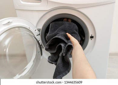 Cropped photo of laundry process. POV of woman hand holding black towel and put it into white washing machine standing inside flat with bright interior