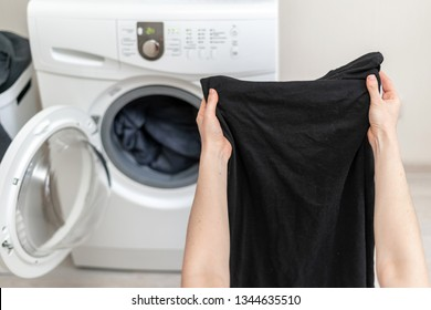 Cropped photo of laundry process. Woman holding black clothes in her hands against white washing machine inside light flat interior