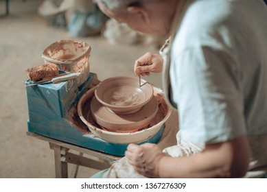 Cropped photo of male potter in apron sitting on chair in workshop. He is making ornament with stick on earthenware while leaning over bowl. Concept of ceramic art and hobby