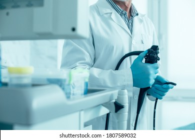 Cropped photo of a man in white coat and rubber gloves standing with a modern endoscope