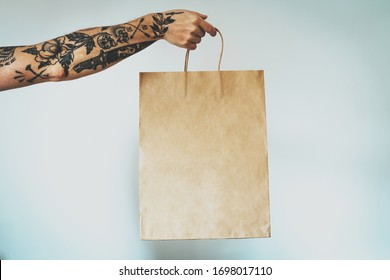cropped photo on a hand with tattoos that holds blank craft paper package, bag mock-up. Empty space for design. White wall background
