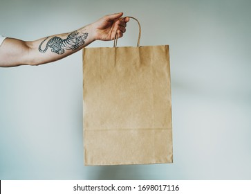 cropped photo on a hand with tattoos that holds craft paper package with empty space for your logo or design, mock-up of shopping bag with handles. White wall background