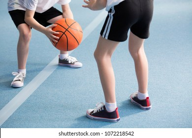 Cropped photo of pupils playing basketball in the gym