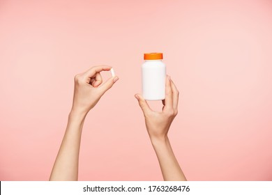 Cropped photo of raised female's well-groomed hands holding white pill and bottle with orange cover, taking vitamins while posing over pink background