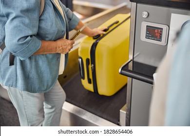 Cropped photo of a senior Caucasian female passenger placing her bag on the conveyor belt