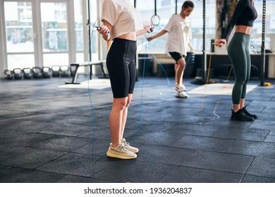 geputztes Foto von schlanken Damen mit Seilen zum Cardio im Fitnessraum