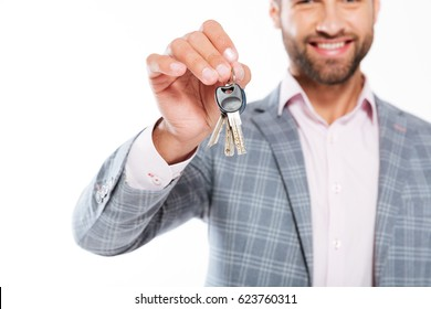 Cropped photo of smiling young man standing isolated over white background and holding keys. Focus on keys.