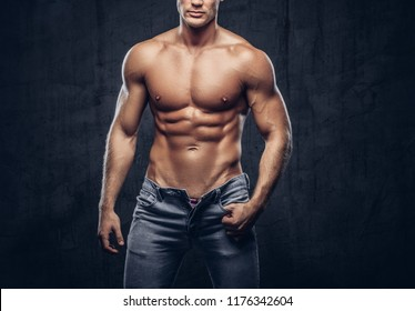 Cropped photo of a sporty guy with muscular body in jeans posing in studio.