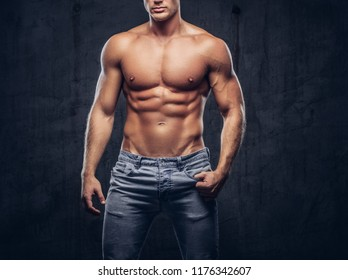 Cropped photo of a sporty guy with muscular body in unbuttoned jeans posing in studio.