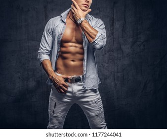 Cropped photo of a sporty man with a muscular body in unbutton shirt and jeans posing in studio.