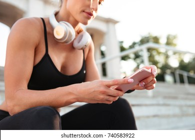 Cropped photo of strong young sports woman sitting on steps listening music and chatting by phone.