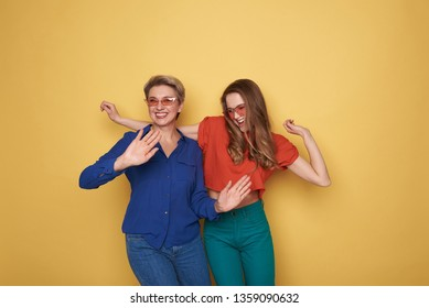Cropped photo of stylish smiling ladies wearing fashionable clothes and situating against orange background. Pretty daughter standing near her mother and having fun together. Cheerful old female