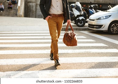 Cropped photo of stylish successful man in business wear walking through pedestrian crossing in downtown with leather male bag in hand