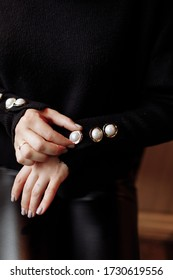 Cropped photo of a stylish woman in black outfit with pearls details. ashion concept.