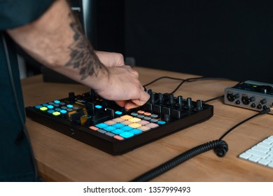Cropped photo tattoo hands of disc jockey master. Man using instrument set for records music in sound recording studio with wooden table and modern interior