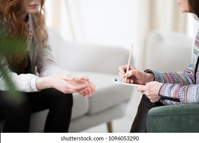 Cropped photo of a therapist writing down notes during therapy with her female patient