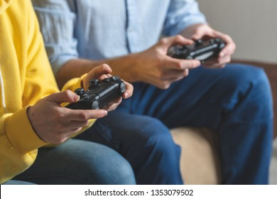 Cropped photo of two unrecognizable person with black modern button joystick in hands. They sitting on comfort sofa and playing in online internet games