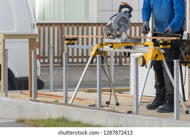Cropped photo of unrecognizable mature handyman working outside of wooden house with a chop saw. He holding measurement in hands