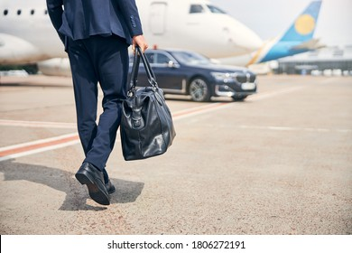 Cropped photo of a well-dressed man with a duffel bag going on a business trip