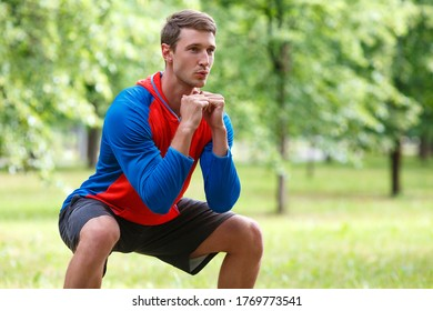 Cropped photo of a young attractive man squatting outdoor in the park. Concept of an active lifestyle and healthy lifestyle.