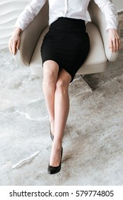 Cropped photo of young business woman sitting in office on chair.