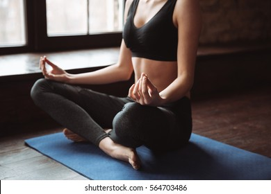 Cropped photo of young fitness woman sitting in gym while make yoga exercises.