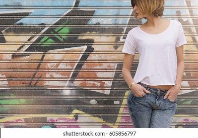 Cropped photo of a young girl wearing in a white blank t-shirt and blue jeans standing on a graffiti wall background. Empty space for you design.