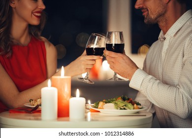 Cropped photo of young lovers having romantic dinner and drinking red wine at home