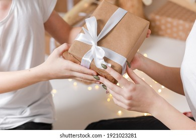 Cropped photo of Young man giving a gift box to his surprised happy woman. party moment. Hands of young boyfriend surprise in box with white ribbon to his girlfriend