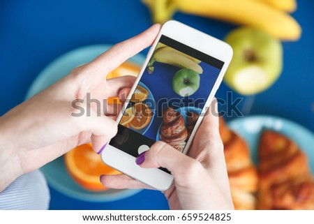 Cropped photo of young redhead lady standing near table indoors take a photo with phone of fruits and croissant.