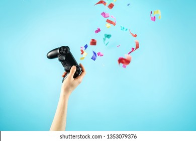 Cropped photo of young woman hand holding black modern analog joystick against bright pastel blue background with funky party celebration confetti