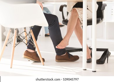 Cropped picture of a couple touching each other with legs under the table
