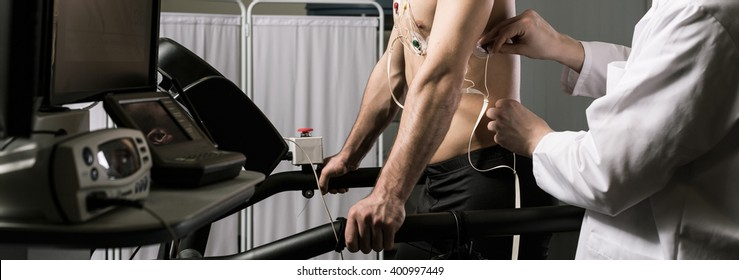 Cropped picture of a doctor checking electrodes on his patient's body