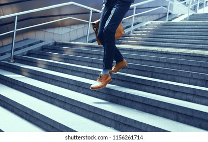 Cropped picture of guy in suit walking down stairs. Businessman dressed in suit and leather shoes walking down concrete steps.