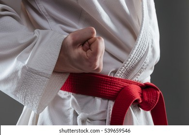 Cropped picture of handsome sportsman dressed in kimono practice in karate and gesture with hand isolated over grey background.
