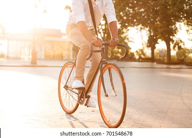Cropped picture of handsome young african man early morning with bicycle walking outdoors.