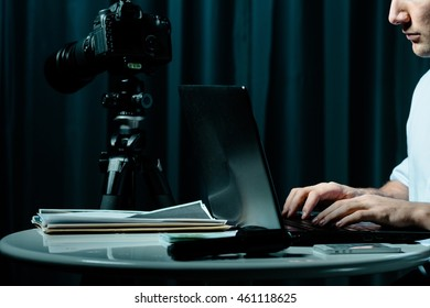 Cropped picture of a man working on his laptop in a room with a camera and a gun