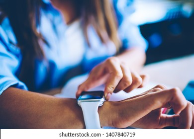 Cropped picture of woman sitting at desktop and checking notification on digital wearable wrist watch, selective focus on female hands and new modern smartwatch looking for time to end of work