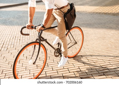 Cropped picture of young african handsome man early morning with bicycle walking outdoors.