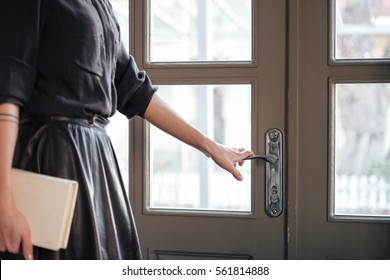 Cropped picture of young beautiful lady open the door in cafe and holding book.