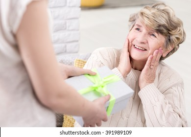 Cropped picture of a young woman giving a present to her suprised grandmother