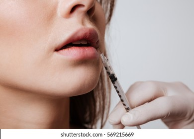 Cropped picture of young woman standing isolated over gray background and increases lips using the syringe.