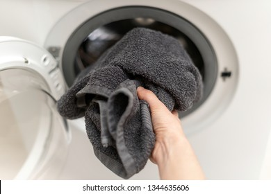 Cropped and point of view photo of laundry process. Calm woman using washing machine to clean black towel. She standing inside bright apartment interior with wipe in hand