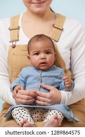 Cropped portrait of adorable little baby girl in jeans dress looking at camera in her mother's arms against pale blue background