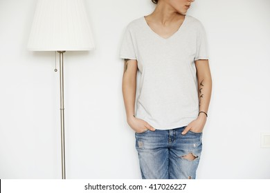 Cropped portrait of beautiful teenage girl looking away while posing against white studio wall wearing blue ripped jeans and oversized gray T-shirt with copy space for your advertising content