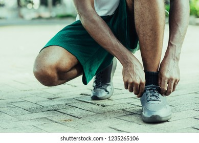 Cropped portrait of black man preparing for jogging outside. Afro American fixing shoelaces before start exercising outdoors. Street workout and fitness concept