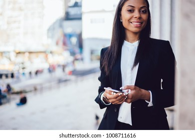 Cropped portrait of charming African American economist in formal elegant wear making money payment on website  via smartphone smiling for the camera. Successful businesswoman posing with cellphone