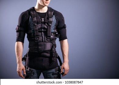 Cropped Portrait of fit Man wearing black suit for ems training standing against blue wall