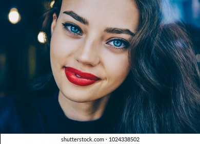 Cropped portrait of gorgeous brunette young woman with beautiful blue eyes and charming smile on face.Close up of Ukrainian attractive female 20 years old with red lips looking at camera and smiling